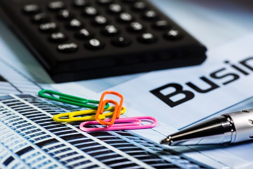 A calculator, pen, and four brightly coloured paperclips sit on a business document.