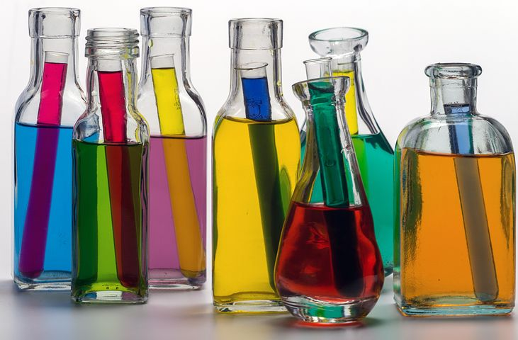 Seven bottles filled with bright transparent fluids stand in a line, each has a vial filled with a different coloured fluid inside it.